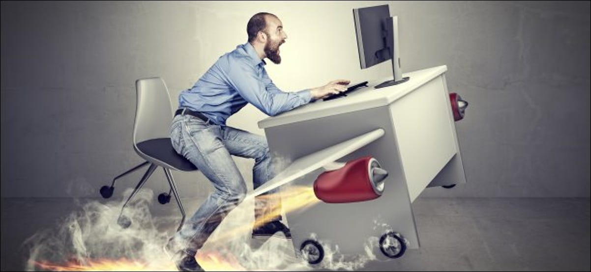 A man using a desktop computer with jet engines strapped to his desk.