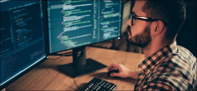 A developer coding on a Linux desktop PC.