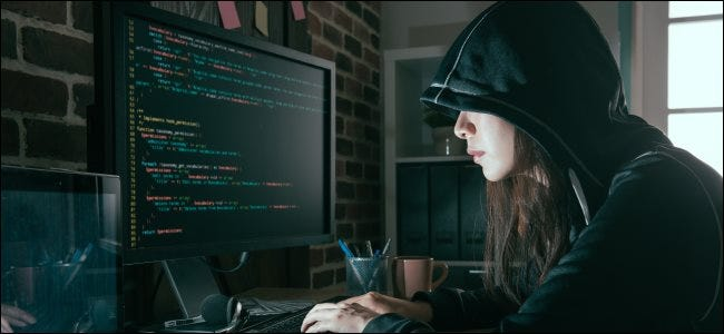 A female hacker typing code on a computer.