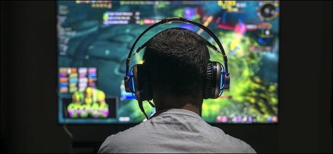 Someone playing a video game on a big-screen TV while wearing headphones.