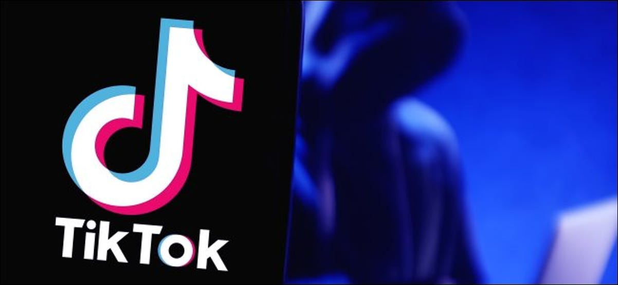 A TikTok logo on a phone whit a figure using a laptop in the background.