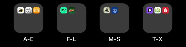 Four folders on an iOS Home screen labeled alphabetically.