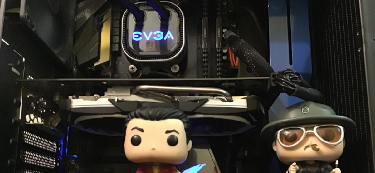 The inside of a desktop PC with two Funko Pop dolls inside the case.