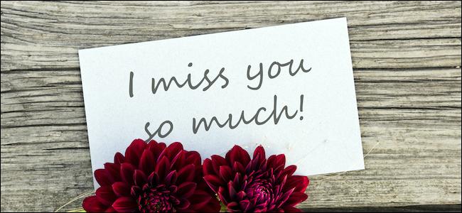 """""""Eu sinto tanto sua falta"""" escrito em uma placa ao lado de flores"""