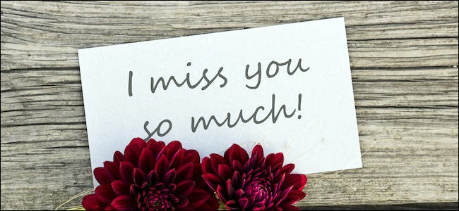 """I miss you so much"" written on a sign next to flowers"