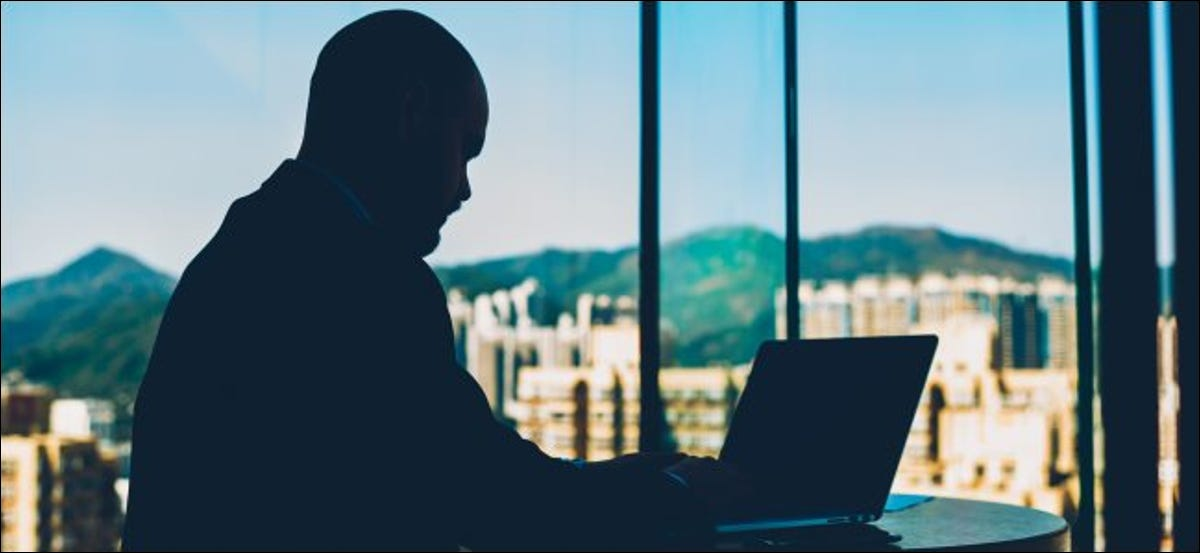 A silhouette of a man browsing on a laptop.