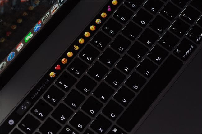 A backlit MacBook Pro keyboard with a touch bar.