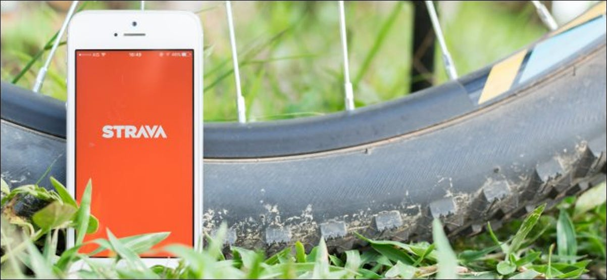 The Strava app on a smartphone next to a bicycle tire.