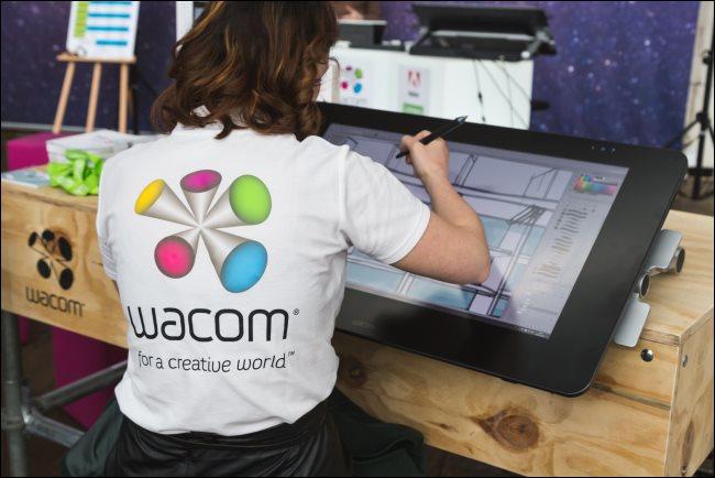 A digital artist working on a large Wacom tablet.