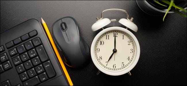 An alarm clock next to a computer keyboard and mouse.