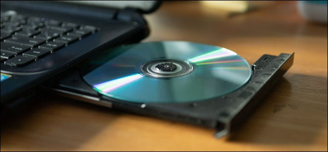 A CD in the tray of a laptop DVD-R drive.