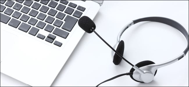 An audio headset with a microphone next to a MacBook keyboard.