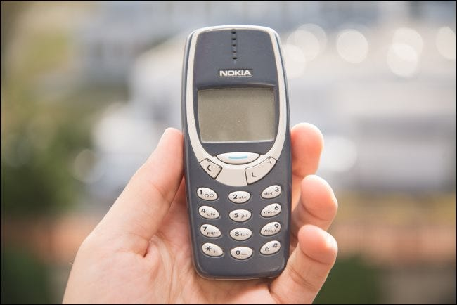 Someone holding a Nokia 3310 phone.