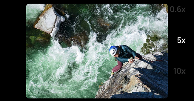 Zoom shot of a man on a rope climbing the rocks next to a rushing river.