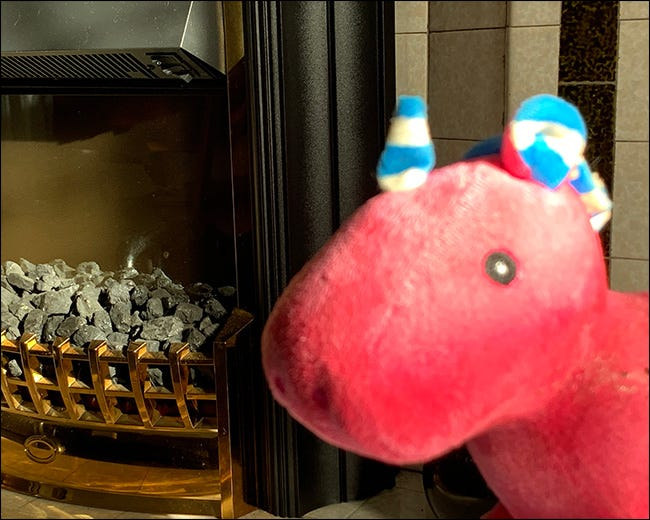 A close-up of a blurry stuffed unicorn with the fireplace behind it in focus, instead.