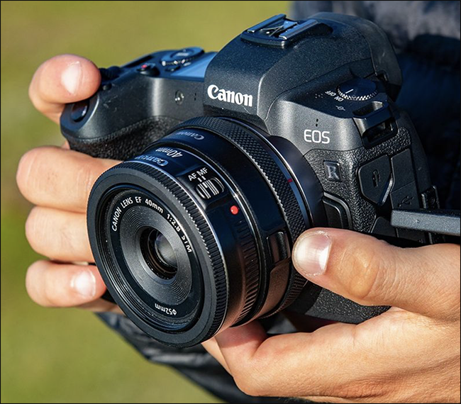 Someone holding a Canon EOS camera with a mirrorless adapter mounted on it.
