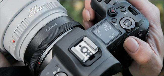 Alguien sosteniendo una cámara Canon con un adaptador sin espejo.