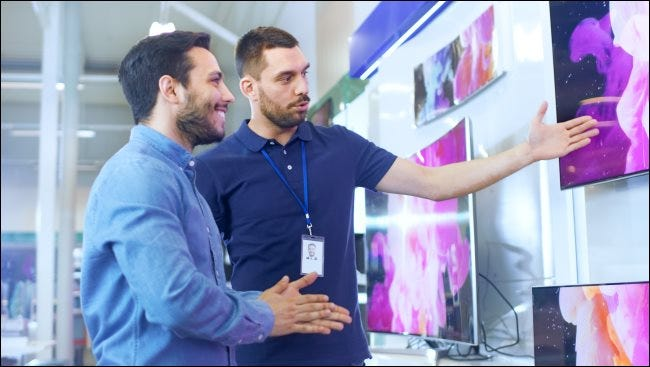 A salesperson showing a TV to a customer in a store.