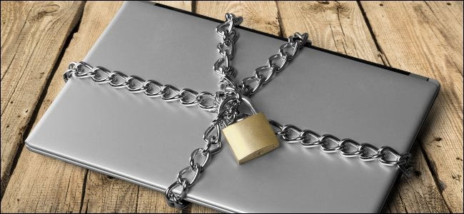 A laptop secured shut with a chain and padlock.