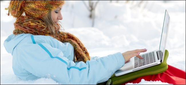 A woman using a MacBook outdoors in snow.