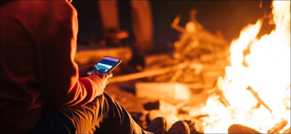 A person using a smartphone in front of a campfire at night.