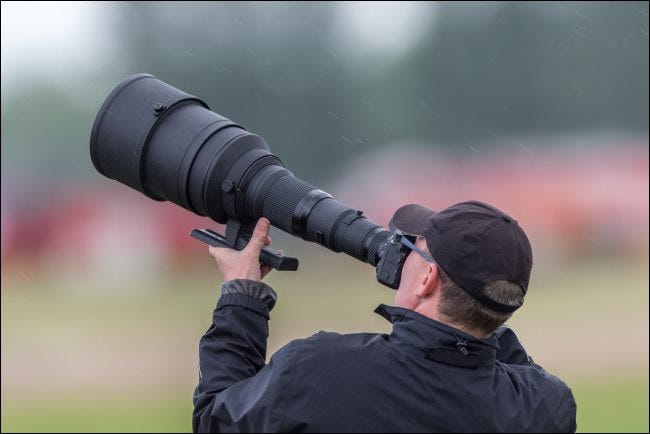 A photographer using a huge telephoto lens.