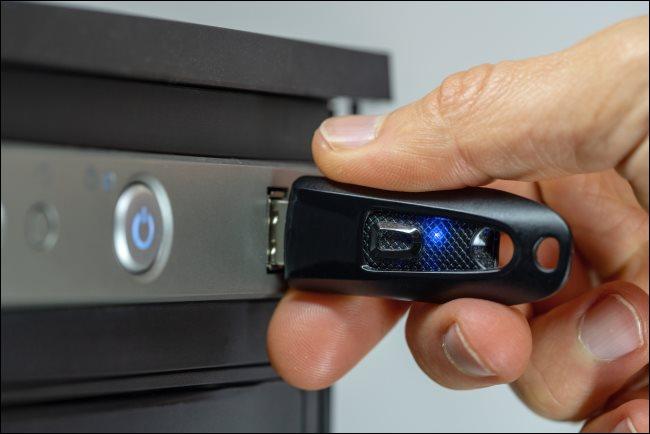 Una mano insertando una unidad flash USB en una computadora de escritorio.