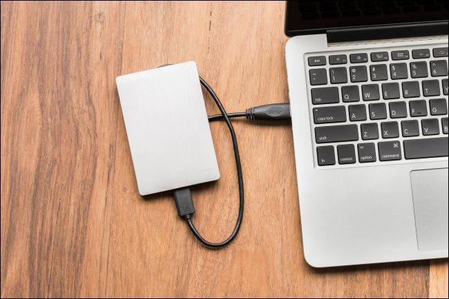 A USB hard drive connected to a laptop.