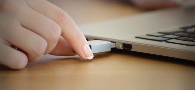 Una mujer conectando una unidad USB a una computadora portátil.