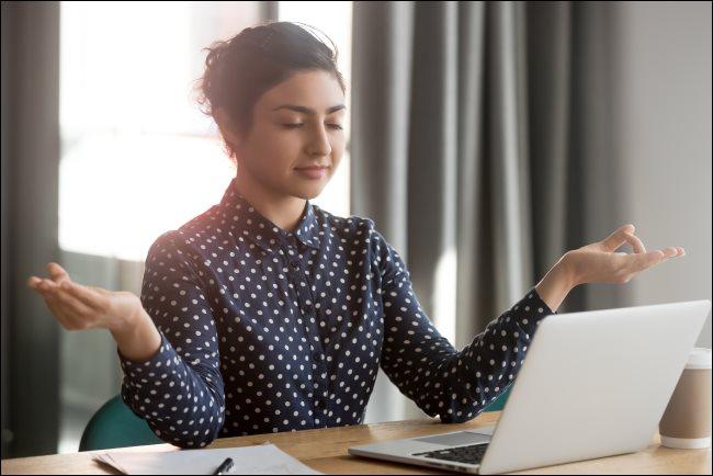 Una mujer meditando frente a un MacBook en una oficina.