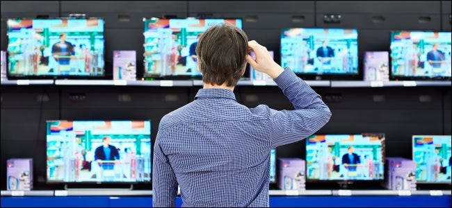 A man scratching his head while looking at a display of TVs in a store.