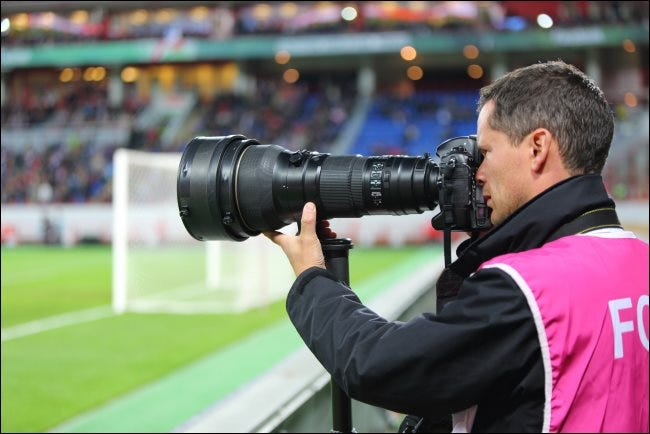 A photographer with a large optical zoom lens at a soccer game.