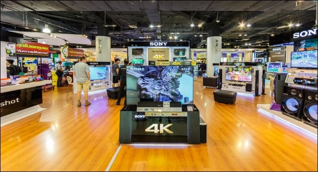 Shoppers looking at 4K TVs in a store.
