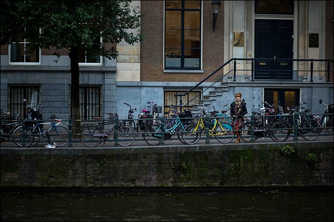 A woman standing on a bridge behind a line of parked bicycles.
