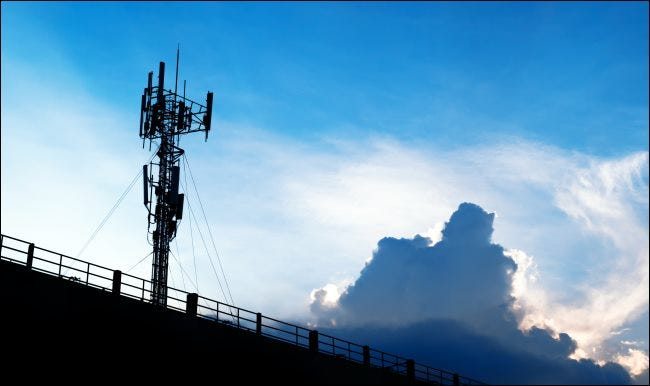 A 5G cellular tower against a blue sky with white clouds.