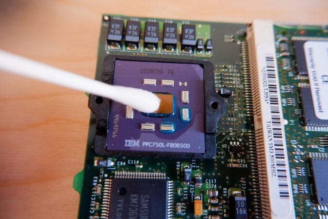 A Q-tip hovering over a computer circuit board.