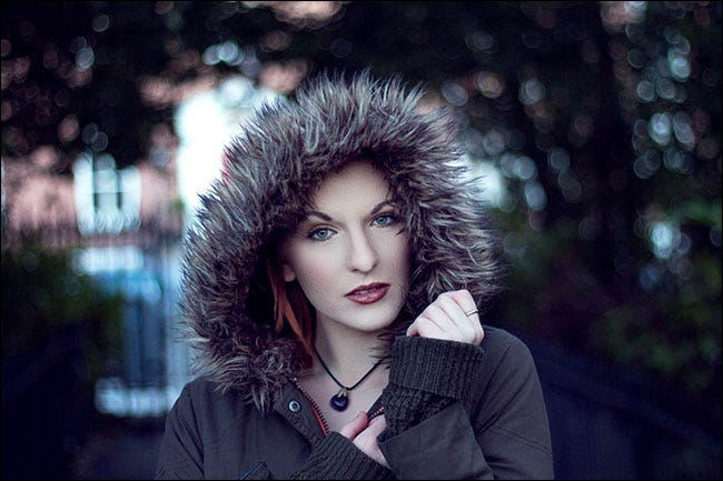 A portrait of a woman wearing a coat with a fur-lined hood in which the background is blurred.