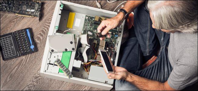 A man assembling a desktop computer on the floor.