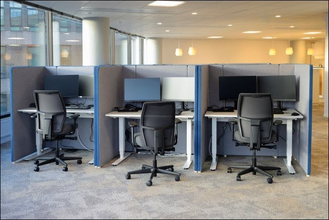 Three cubicles with matching chairs and computer monitors on the desks.