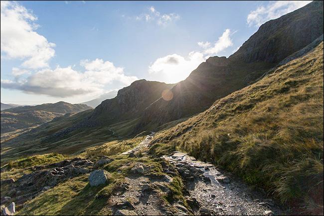 The sun shining over a mountain, creating lens flare.