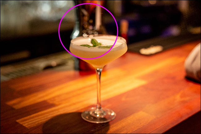 A cocktail glass on a bar with polygonal bokeh in the middle.