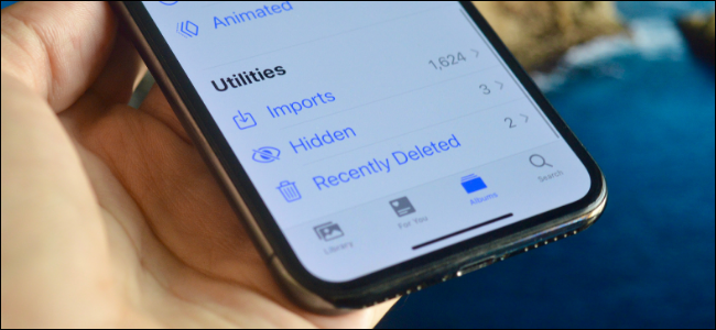 "Someone holding an iPhone showing the ""Hidden"" folder under ""Utilities."""