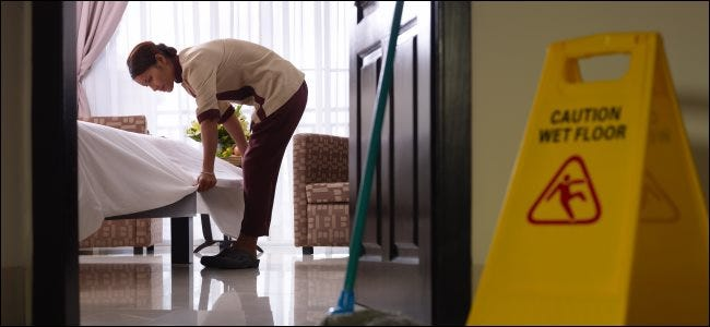 A maid tidying up a bed in a hotel room.