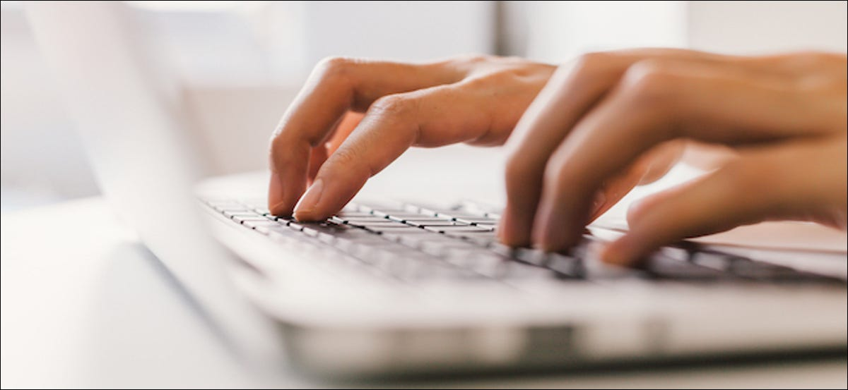 Person typing on a laptop keyboard