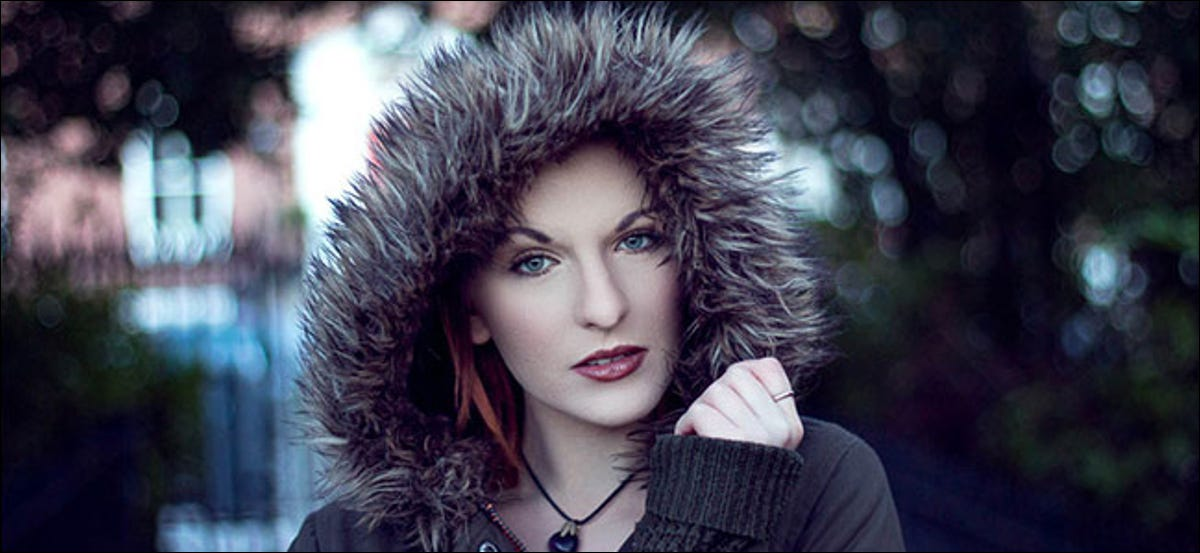 A portrait of a woman wearing a furred hood with a blurred background.