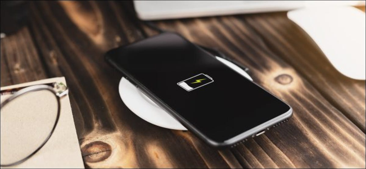 A smartphone charging on a wireless charging pad.