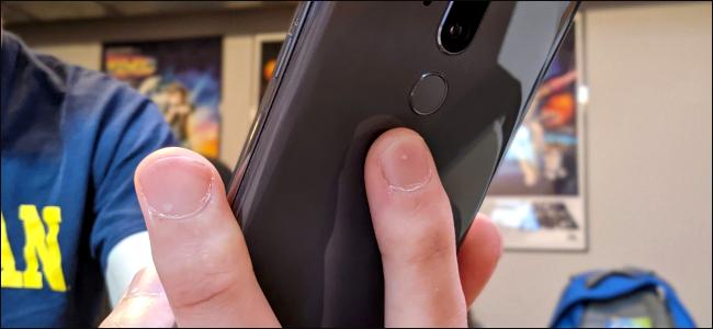 Los dedos de alguien en la parte posterior de un teléfono Android.