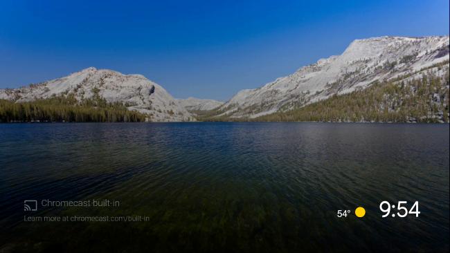 Lo screen saver predefinito di Android TV di un lago circondato da montagne.