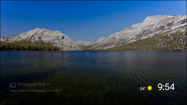 The default Android TV screen saver of a lake surrounded by mountains.