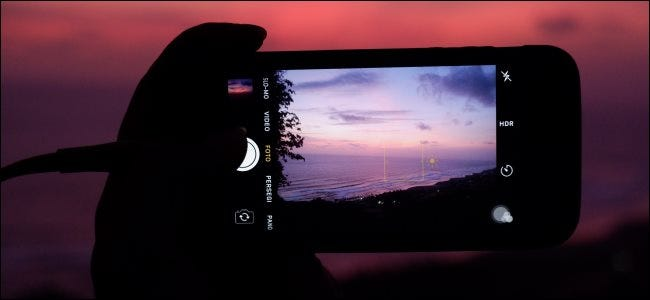 Someone taking a picture of a sunset at dusk with an iPhone.